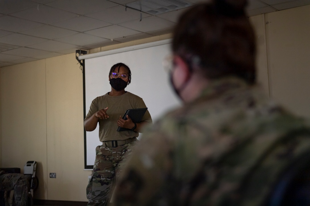 A photo of an Airman speaking to another Airman