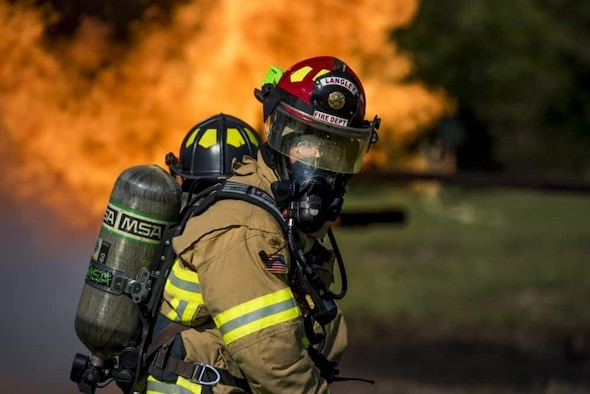 a photo of a fire fighter with his helmet and mask on in-front of a fire