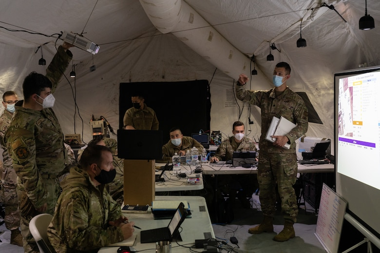 A group of Airmen standing in a large tent.