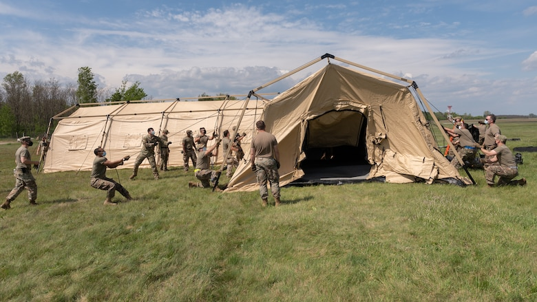 A group of Airmen setting up a large tent.