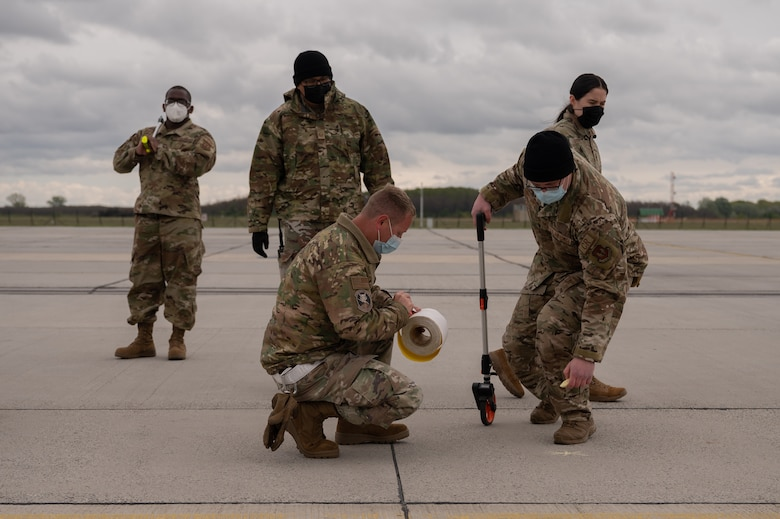 A group of Airmen standing and kneeling to mark spots on an airfield.