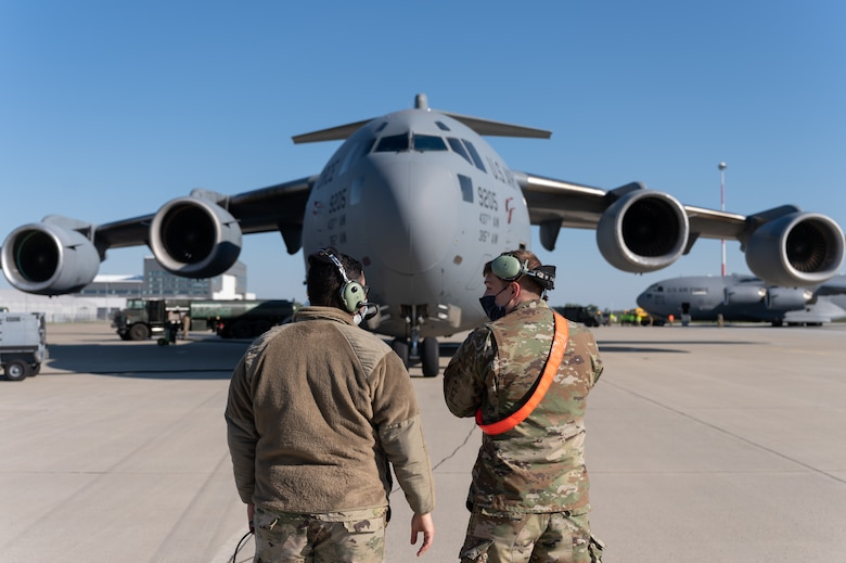 Two Airmen standing in front of an aircraft.