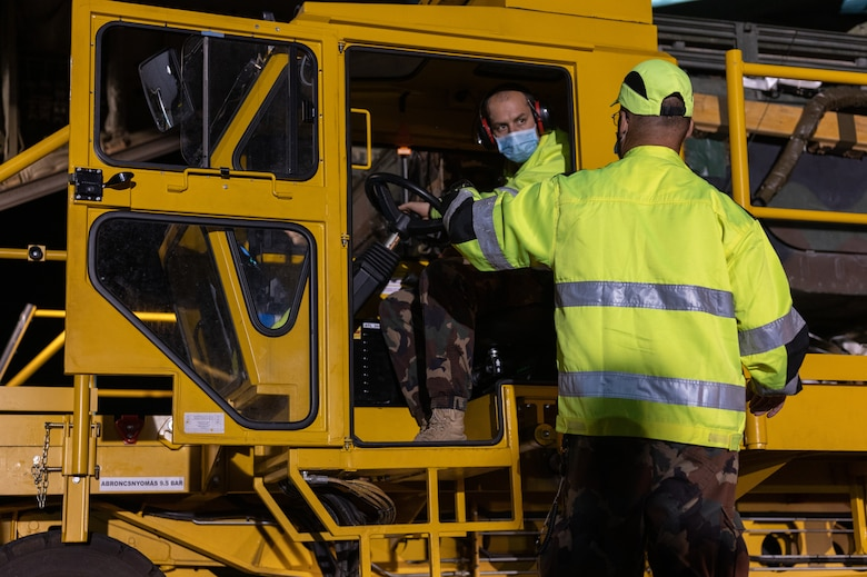 A man in a K-loader talking to a man standing outside the vehicle.