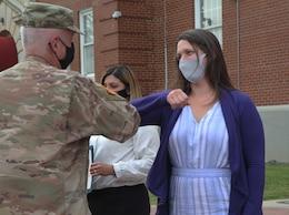 woman elbow bumps commanding general after receiving award