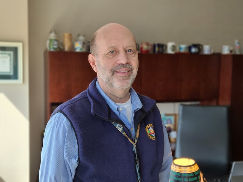A man in a blue button up shirt and blue fleece vest stands in his office.