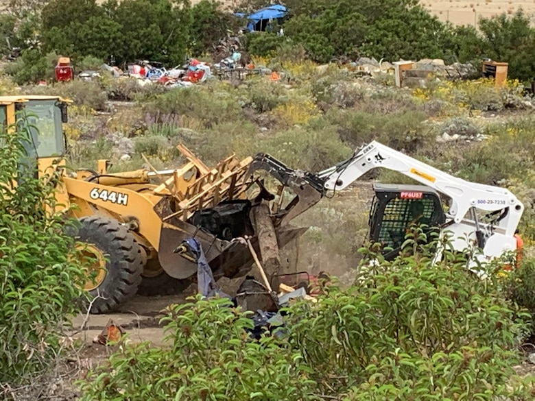 A small tracked skid steer pushes a load of debris to a loader, May 10, below the Santa Fe Dam in Irwindale, California. The cleanup by the U.S. Army Corps of Engineers Los Angeles District was done in five days.