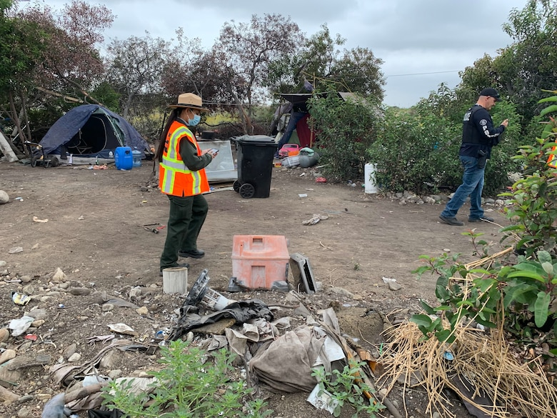 Park Ranger Annel Monsalvo, U.S. Army Corps of Engineers Los Angeles District, investigates one of dozens of abandoned campsites below the Santa Fe Dam, May 10, before crews arrive to clear out the debris.