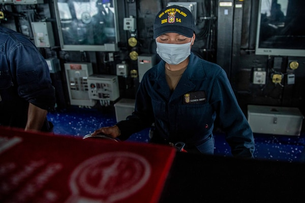 Boatswain's Mate Seaman Elizabeth Sanchez, from Houston, mans the helm on the bridge of the Arleigh Burke-class guided-missile destroyer USS Curtis Wilbur (DDG 54) as the ship conducts routine operations. Curtis Wilbur is assigned to Commander, Task Force 71/Destroyer Squadron (DESRON) 15, the Navy's largest forward DESRON and the U.S. 7th Fleet's principal surface force.