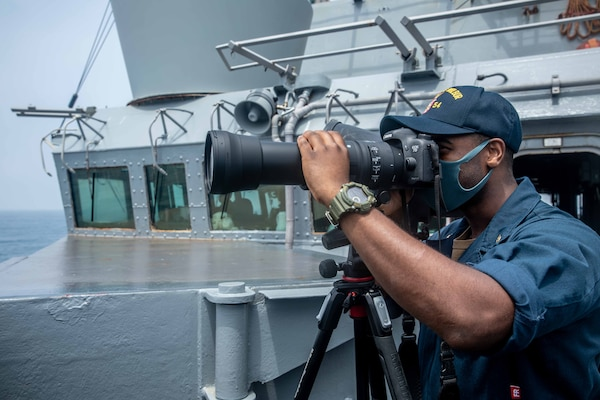 Intelligence Specialist Chief Michael Tolbert, from Moss Point, Miss., stands watch on the bridge while the Arleigh Burke-class guided-missile destroyer USS Curtis Wilbur (DDG 54) conducts routine operations. Curtis Wilbur is assigned to Commander, Task Force 71/Destroyer Squadron (DESRON) 15, the Navy's largest forward DESRON and the U.S. 7th Fleet's principal surface force.