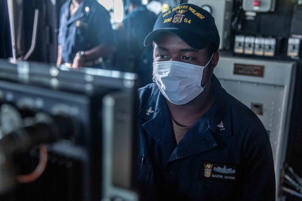 Gunner's Mate 2nd Class Marvin Harris, from Chicago, stands watch on the bridge of the Arleigh Burke-class guided-missile destroyer USS Curtis Wilbur (DDG 54) as the ship conducts routine operations. Curtis Wilbur is assigned to Commander, Task Force 71/Destroyer Squadron (DESRON) 15, the Navy's largest forward DESRON and the U.S. 7th Fleet's principal surface force.