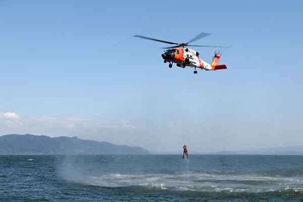 An MH-60 Jayhawk helicopter crew from Coast Guard Sector Columbia River hoists an aviation survival technician from the Columbia River during rescue training in Warrenton, Oregon, Tuesday, Apr.. 20, 2021. Coast Guard responders train to keep proficient and ready to respond at a moments notice to a call for help. U.S. Coast Guard photo by Petty Officer 1st Class Cynthia Oldham.