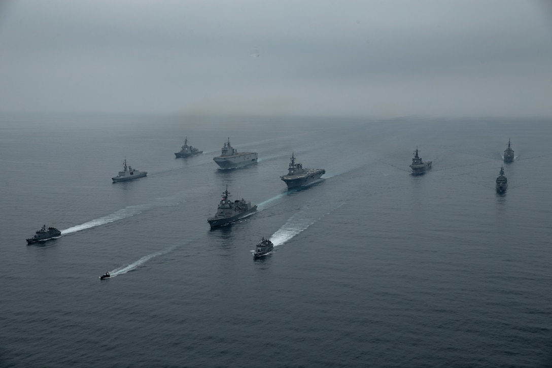 A group of military ships move through the water.