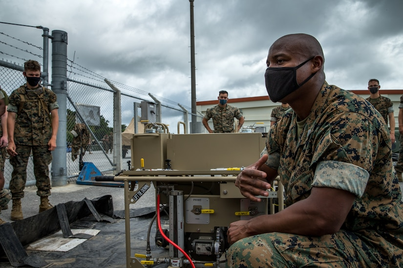 A Marine sits next to equipment while speaking to other Marines.