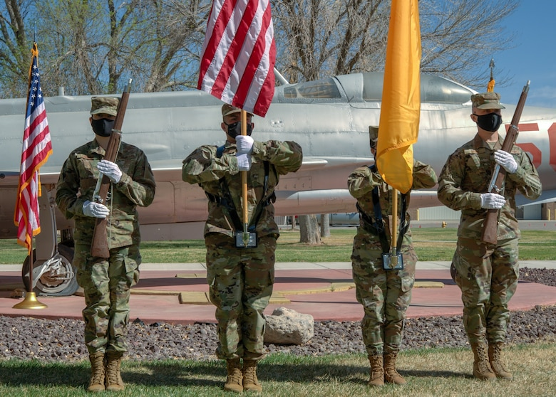 An honor guard stands in from of a static aircraft during a promotion ceremony.