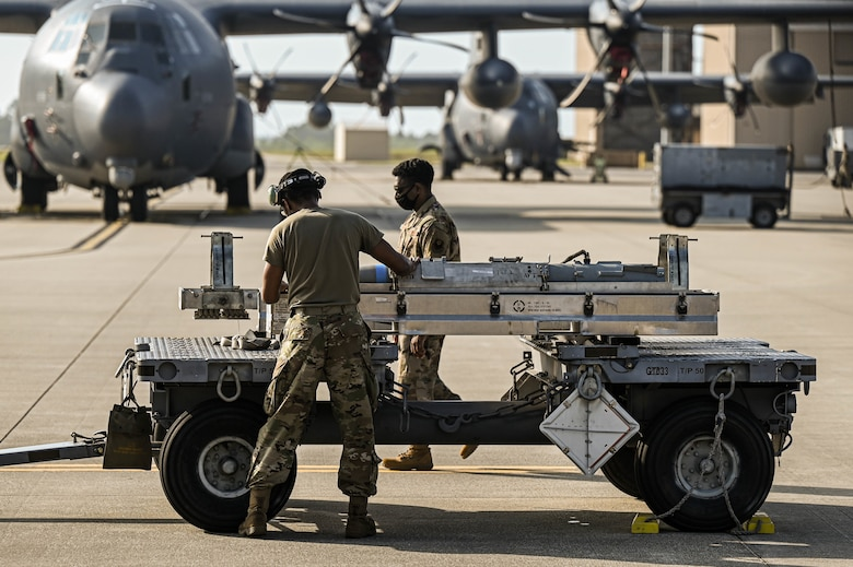 U.S. Air Force Airman 1st Class Michael Slaughter, a weapons load crew member with the 4th Aircraft Maintenance Unit, is evaluated by another Air Commando while delivering a guided bomb unit to an AC-130W AC-130W Stinger II gunship.