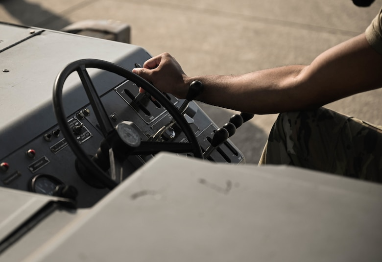 U.S. Air Force Airman 1st Class Michael Slaughter, a weapons load crew member with the 4th Aircraft Maintenance Unit, operates machinery while delivering a guided bomb unit to an AC-130W Stinger II gunship.
