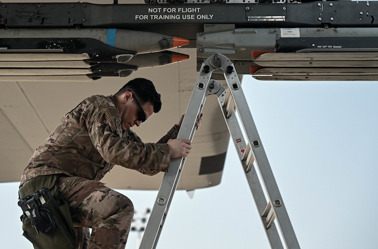 U.S. Air Force Staff Sgt. Daniel Buruato, a weapons load crew chief with the 4th Aircraft Maintenance Unit, dismounts from a ladder.