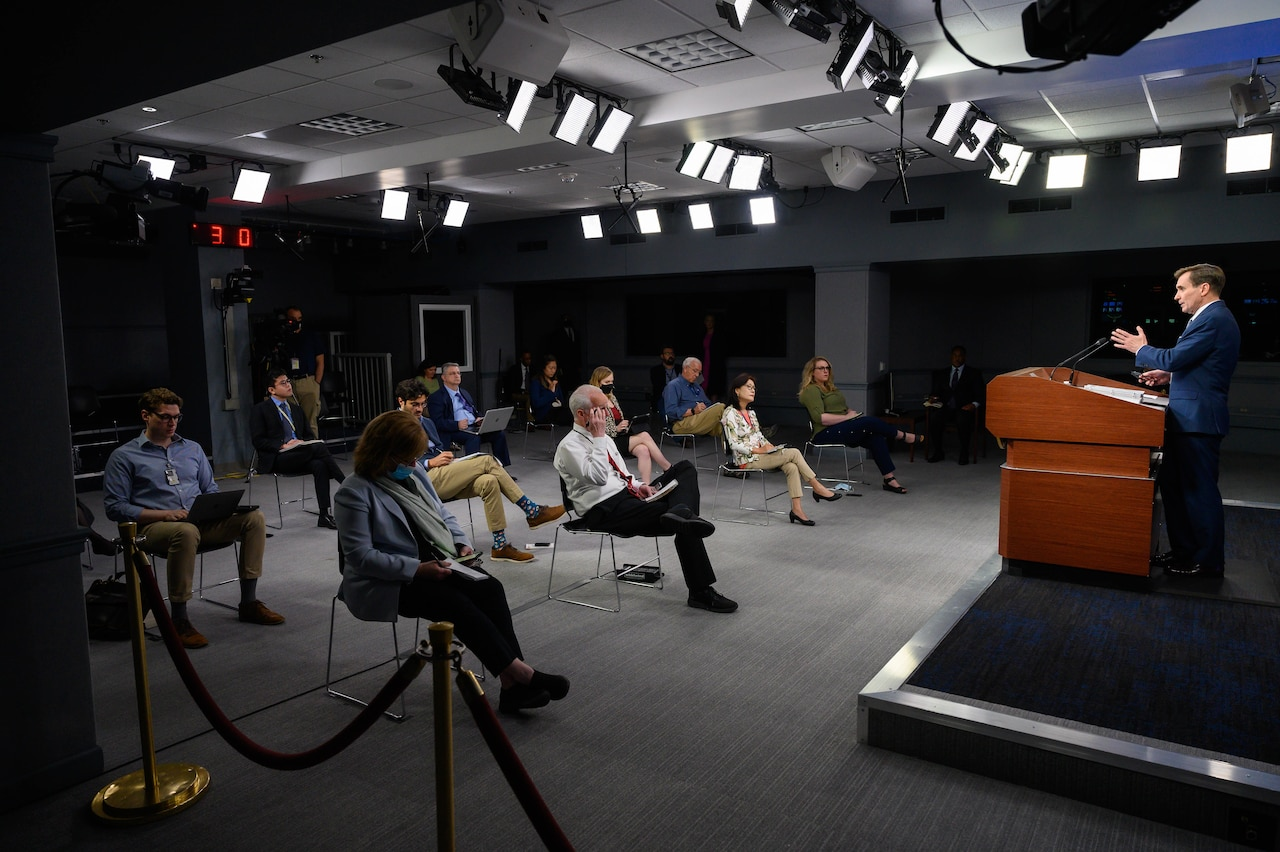 A man answers reporters questions during a press briefing.