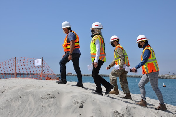 U.S. Army Corps of Engineers Los Angeles District commander Col. Julie Balten with two members of her team, follow a contractor into the construction zone at the mouth of Oceanside Harbor, April 12. Sand dredged from the harbor will be piped to a section of Oceanside Beach, California. The annual maintenance dredging of Oceanside Harbor is contracted and supervised by the U.S. Army Corps of Engineers Los Angeles District.