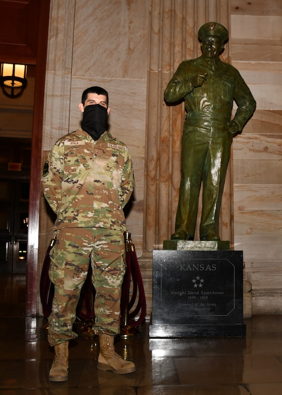U.S. Air Force Senior Airman Dorian Ayala, an avionics test station technician with the 104th Fighter Wing Maintenance Squadron, poses for a photo in front of the Dwight D. Eisenhower statue in the United States Capitol building in Washington, D.C., May 13, 2021. The National Guard has been requested to continue supporting federal law enforcement agencies with security, communications, medical evacuation, logistics and safety support to state, district and federal agencies through mid-May. (U.S. Air National Guard photo by Staff Sgt. Hanna Smith)