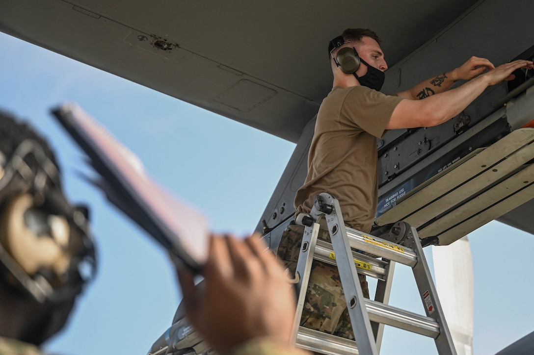 Senior Airman Paul Seagraves, a weapons load crew member with the 4th Aircraft Maintenance Unit, secures a guided bomb unit to an AC-130W Stinger II gunship.