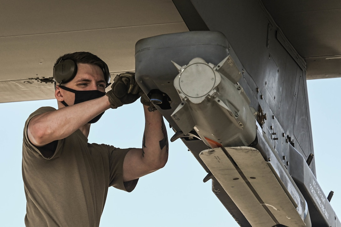 U.S. Air Force Senior Airman Paul Seagraves, a weapons load crew member with the 4th Aircraft Maintenance Unit, secures a guided bomb unit to an AC-130W Stinger II gunship.