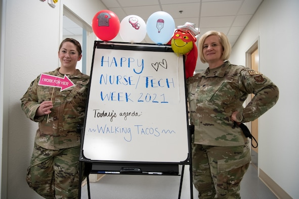 Tech. Sgt. Kylle Hannan, NCOIC of education and training, 90th Medical Group, and Lt. Col. Erin Knightner, 90th Operational Medical Readiness Squadron commander, highlight a whiteboard celebrating National Nurses Week on F.E. Warren Air Force Base, Wyoming, May 6, 2021. The 90 MDG celebrates National Nurses Week to recognize medical staff for their efforts. (U.S. Air Force photo by Airman 1st Class Charles Munoz)