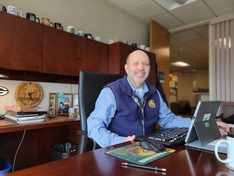 A man in a blue button up shirt and blue fleece vest sits at his desk in his office.
