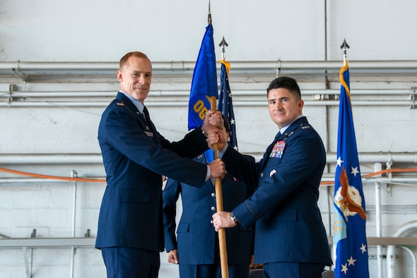 Col. Benjamin Jonsson, 6th Air Refueling Wing commander, passes the 6th Operations Group (OG) guidon to Col. Jonathan Burdick, the incoming 6th OG commander, during the 6th OG's Change of Command ceremony at MacDill Air Force Base, Florida, May 17, 2021. The passing of the unit guidon to Burdick signifies the beginning of his command of the 6th OG. (U.S. Air Force photo by Airman 1st Class David D. McLoney)