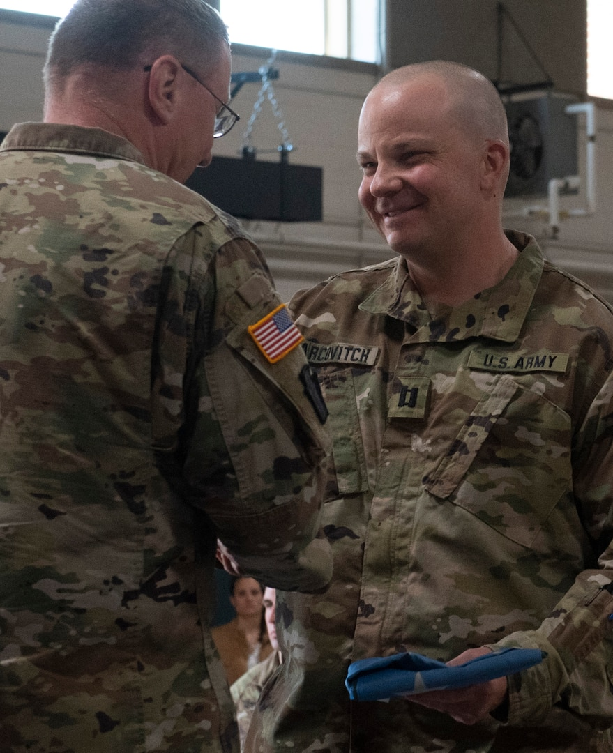 Capt. Mikel Arcovitch, commander of the 172nd Public Affairs Detachment, receives a Vermont battle flag from Maj. Gen. Greg Knight, the state adjutant general, during a sendoff ceremony for Task Force Mansfield and the 172nd PAD at Camp Johnson, Vermont, May 18, 2021. The 172nd PAD will document U.S. Army operations in the U.S. European Command area of responsibility. (U.S. Army National Guard photo by Don Branum)