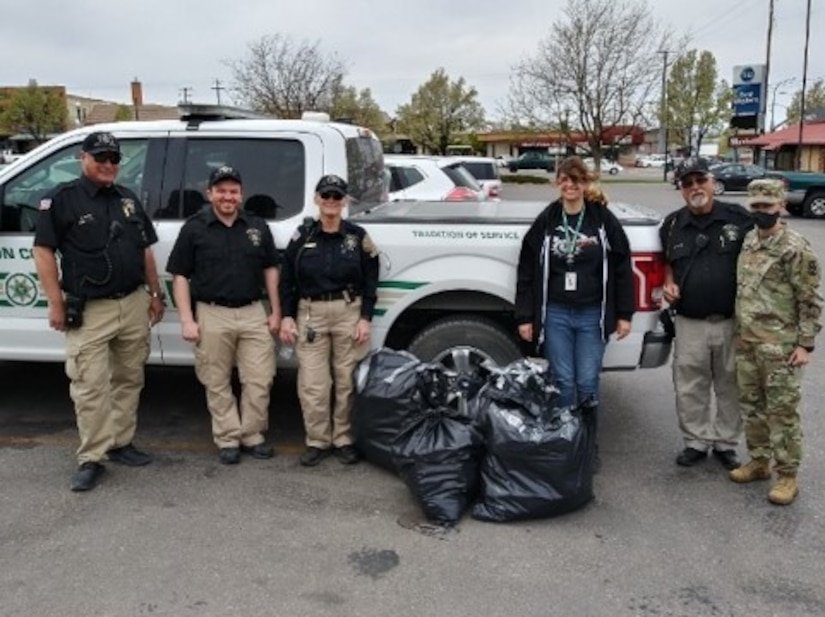 Police, a soldier and civilians pose for photo with garbage bags of prescriptions.