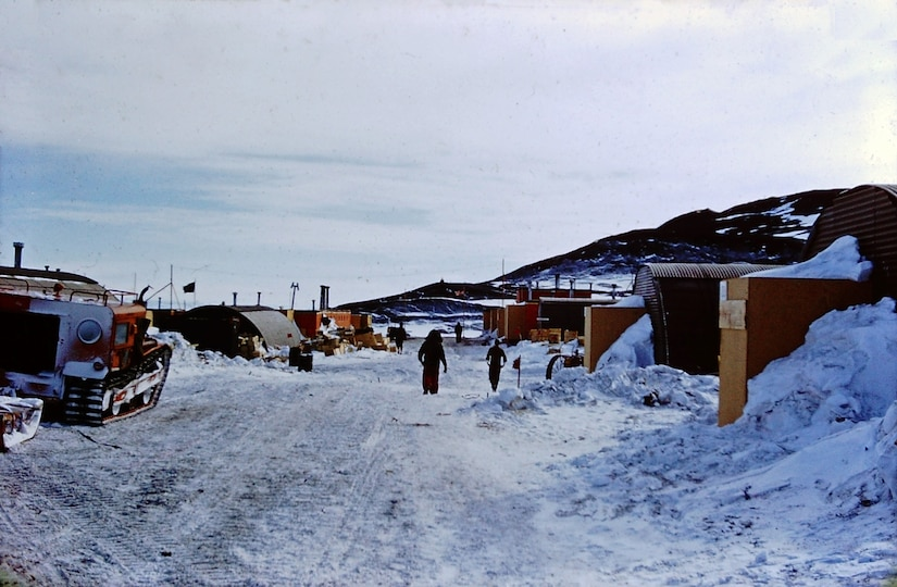 Two people walk a small snow-covered road surrounded by small buildings and a mountain.