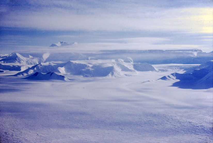 An aerial view of land shows vast snow-covered plains and mountains.