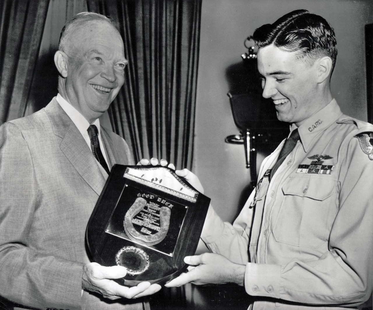 Two men smile while they hold a plaque.