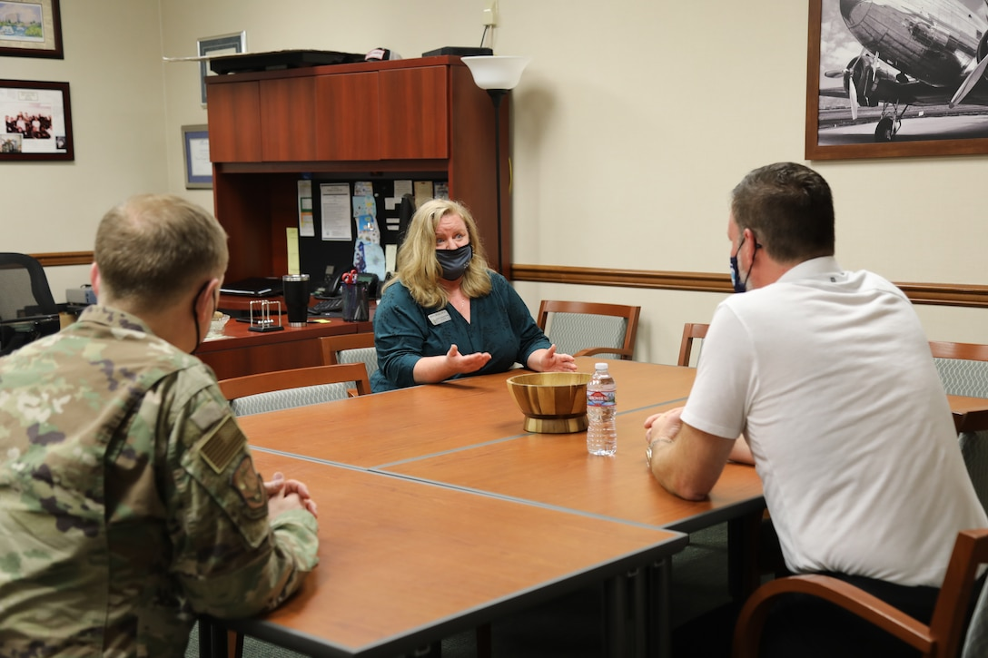 Mayor Andy Ryder, of the City of Lacey, Washington (right), and Col. Paul Skipworth, wing commander of the 446th Airlift Wing (left), speak with Kristi McCann, Director of Psychological Health for the 446th Airlift Wing, about resiliency and Airmen support services during a visit on May 10, 2021, at Joint Base Lewis-McChord, Washington.