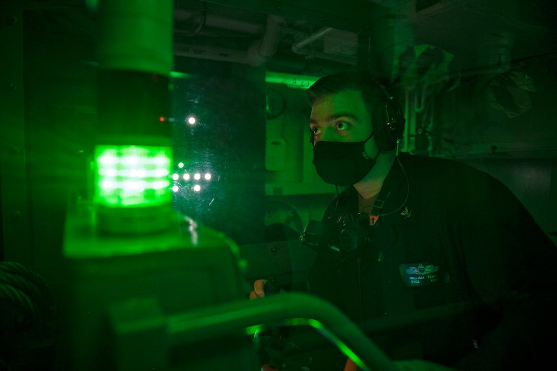 A sailor monitors a board aboard a ship bathed in green light.
