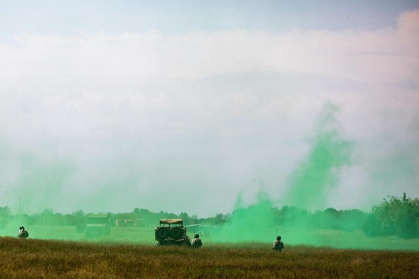 Troops train using green smoke in a field.