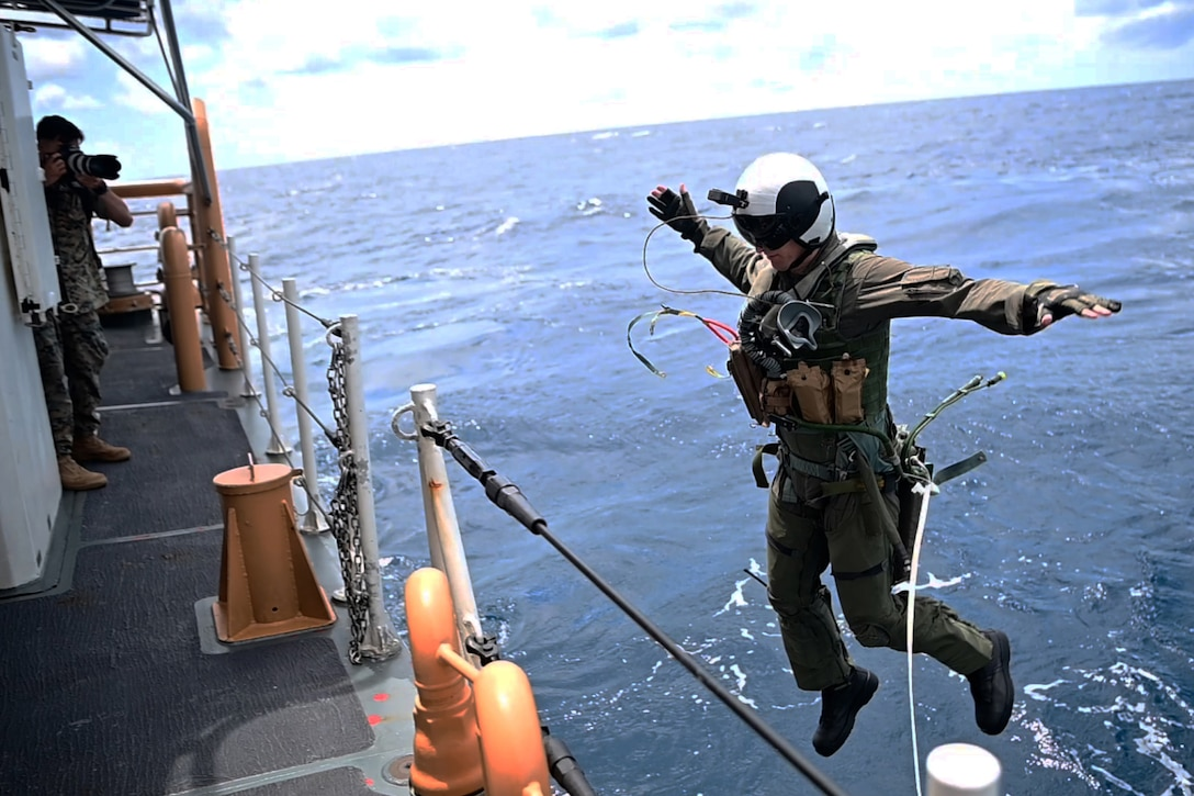 A Marines jumps off a ship into a body of water.