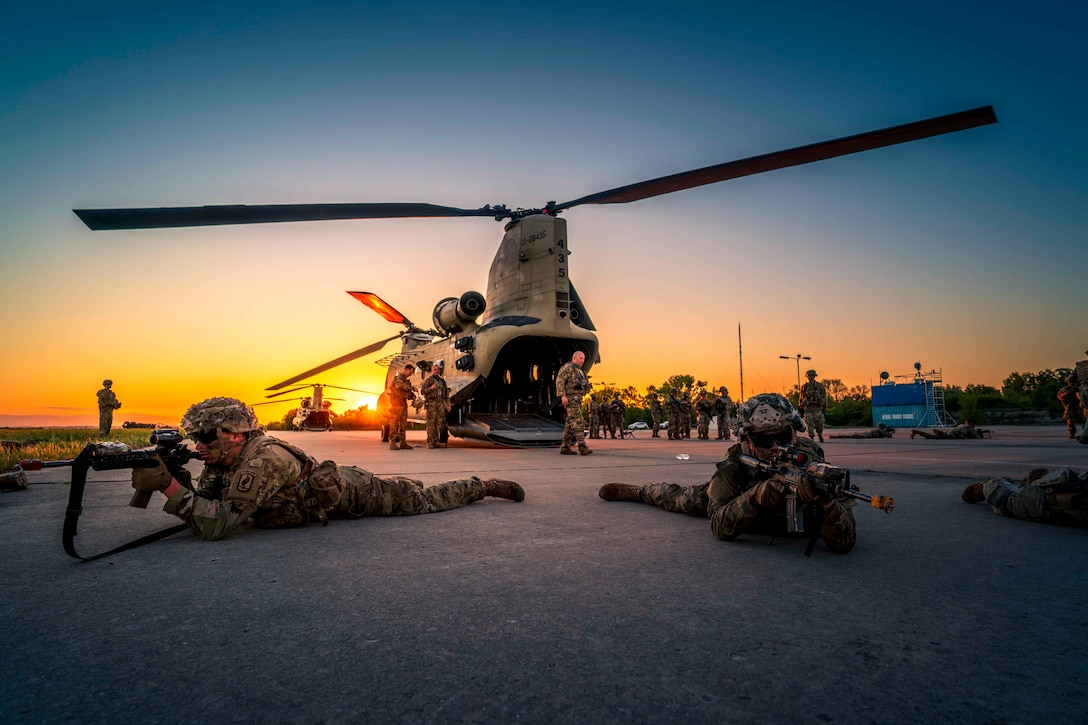 Two soldiers lie on the ground pointing weapons; parked helicopters and other soldiers can be seen behind.