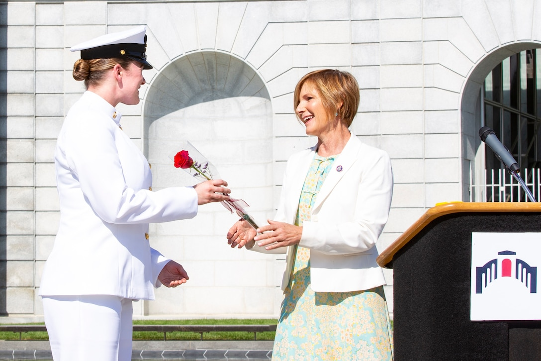 A sailor accepts a rose from a person next to a podium.