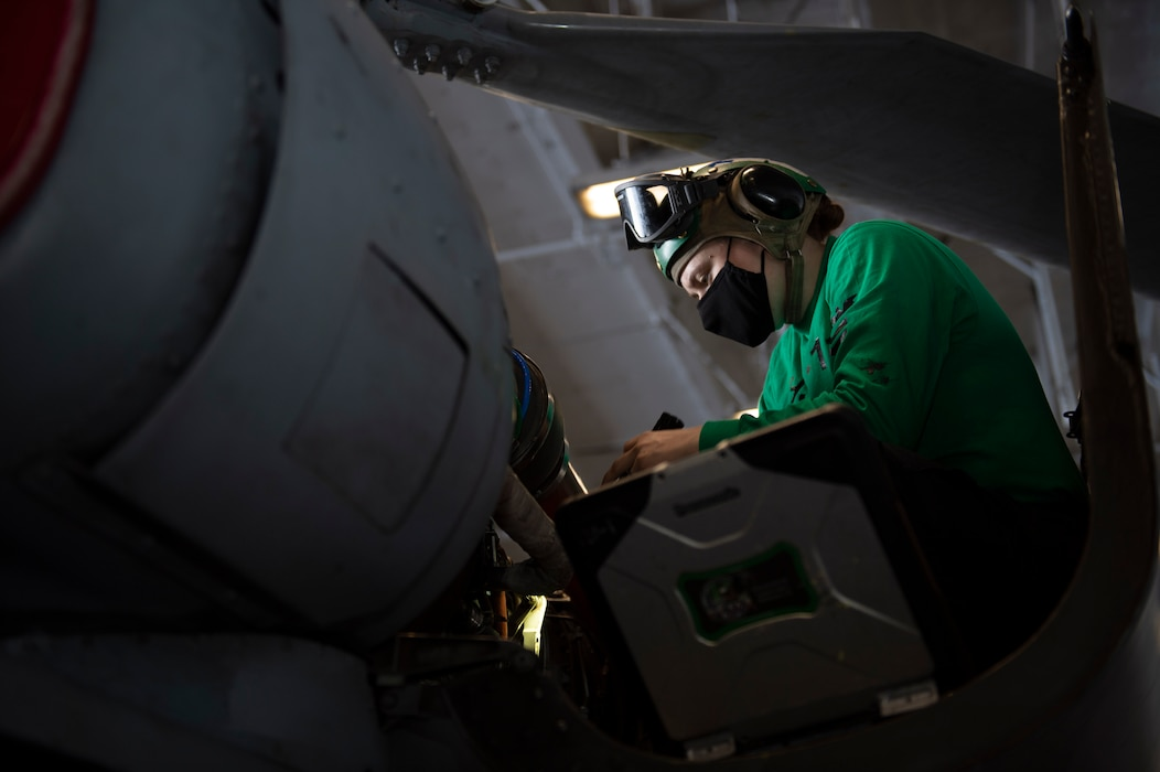 """Aviation Machinist Mate 2nd Class Laurel Rinehart, from Great Falls, Montana, assigned to the """"Dragon Slayers"""" of Helicopter Sea Combat Squadron (HSC) 11, inspects the engine of an MH-60S Sea Hawk helicopter for corrosion in the hangar bay of the Nimitz-class aircraft carrier USS Harry S. Truman (CVN 75) during sea trials after completing an extended carrier incremental availability."""