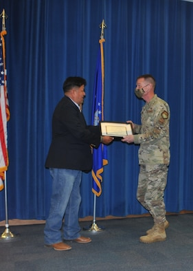 Native American man presents certificate to U.S. Air Force colonel.
