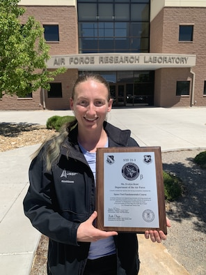 Air Force Research Laboratory engineer Evelyn Kent holds her Space Test Fundamentals course diploma with the AFRL Space Vehicles Directorate headquarters at Kirtland AFB, N.M in the background. Kent graduated from the inaugural space test course earlier this year. (Courtesy photo)