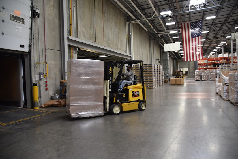 A forklift drives a pallet of packages onto the back of a truck.