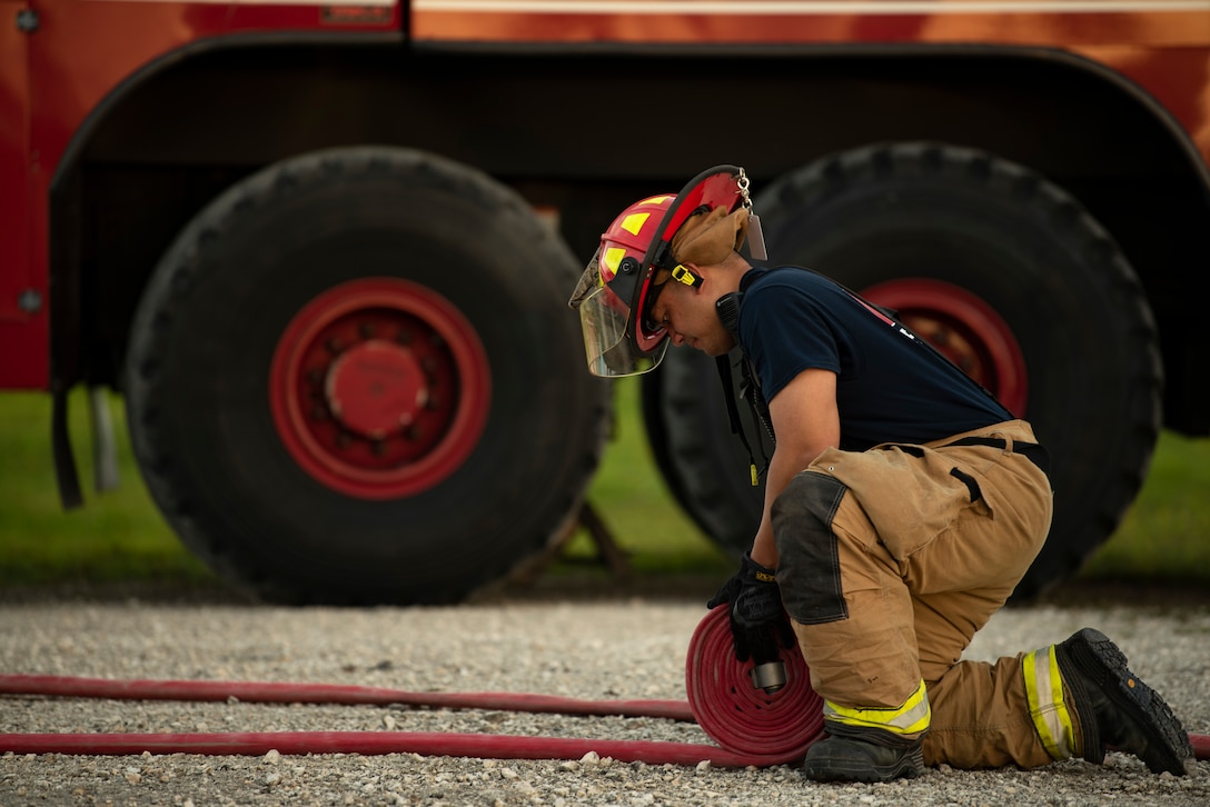 U.S. Air Force firefighter assigned to the 36th Civil Engineer Squadron, rolls up a fire hose during joint aircraft fire training at Andersen Air Force Base, Guam, May 11, 2021.
