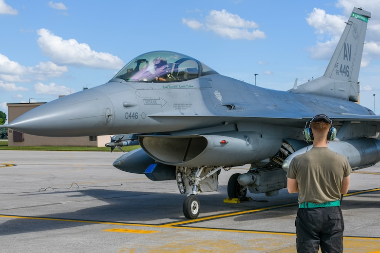 Senior Airman Neil Farbotnik, 555th Aircraft Maintenance Unit F-16 Fighting Falcon crew chief, marshals in an F-16 participating in Astral Knight 2021 (AK21) at Aviano Air Base, Italy, May 18, 2021. Eight F-16s assigned to the 555th Fighter Squadron are participating in AK21, which is a joint, multinational exercise designed to test integrated air and missile defense capabilities. AK21 aims to demonstrate the integration, coordination and interoperability of joint existing command and control. (U.S. Air Force photo by Airman 1st Class Brooke Moeder)