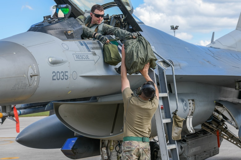 U.S. Air Force Maj. John Hamilton, 555th Fighter Squadron F-16 Fighting Falcon pilot, hands a flight equipment bag to Senior Airman Juan Monroy, 555th Aircraft Maintenance Unit F-16 crew chief, after participating in Astral Knight 2021 (AK21) at Aviano Air Base, Italy, May 18, 2021. AK21 is a U.S. Air Forces in Europe-Air Forces Africa-led exercise involving Airmen, Soldiers and Sailors from the U.S. working with members from Albania, Croatia, Greece, Italy and Slovenia. AK21 is an integrated air and missile defense exercise focused on defending key terrain. (U.S. Air Force photo by Airman 1st Class Brooke Moeder)