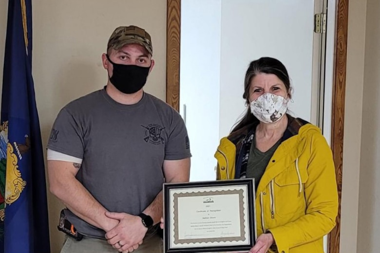 TSgt. Nathan Bourn, a munitions specialist assigned to the 158th Fighter Wing, is recognized by Beth Saradarian, executive director of the Rutland County Humane Society at the Poultney Fire Department, Poultney, VT.