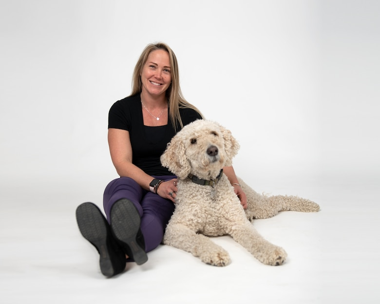 Mrs. Trish Soter, Director of Psychological Health, assigned to the 158th Fighter Wing, poses with the base therapy dog, Beau.