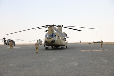 Task Force Phoenix personnel walk out to their aircraft on flight line at Camp Buehring, Kuwait.